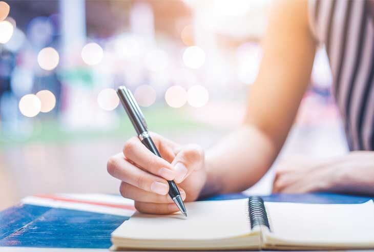 Woman writing notes for a book in journal